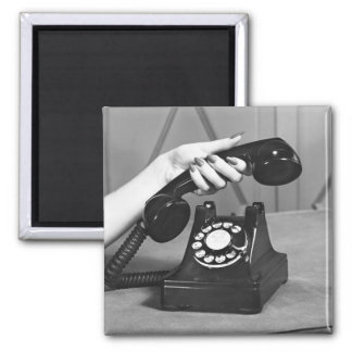 Woman picking up phone close up of hand magnet