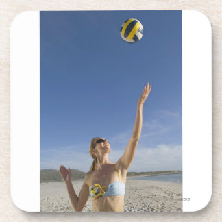 Woman playing volleyball on beach drink coaster