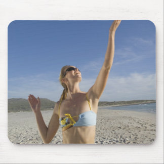 Woman playing volleyball on beach mouse pad