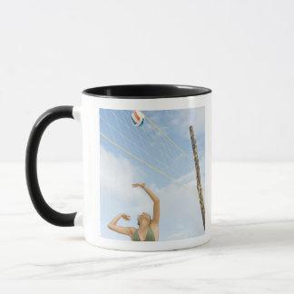 Woman playing volleyball outdoors mug