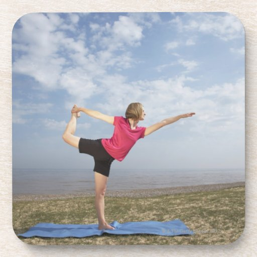 Woman practicing yoga by the beach beverage coaster