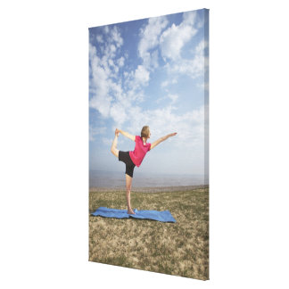 Woman practicing yoga by the beach canvas print