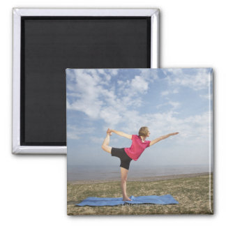 Woman practicing yoga by the beach magnet
