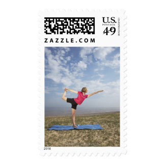 Woman practicing yoga by the beach stamps