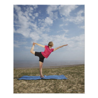 Woman practicing yoga by the beach poster