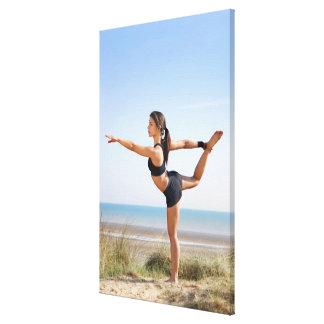 Woman practicing yoga on beach canvas print