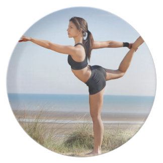 Woman practicing yoga on beach party plates
