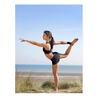 Woman practicing yoga on beach postcard