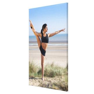 woman practicing yoga on beach wearing canvas print