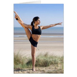 woman practicing yoga on beach wearing card