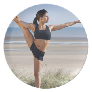 woman practicing yoga on beach wearing party plates