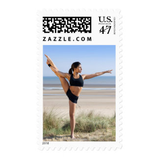 woman practicing yoga on beach wearing postage