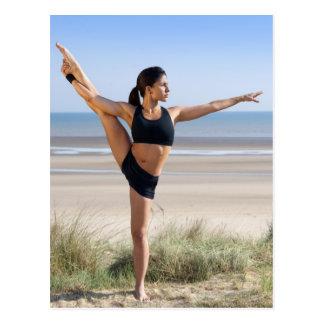 woman practicing yoga on beach wearing postcard