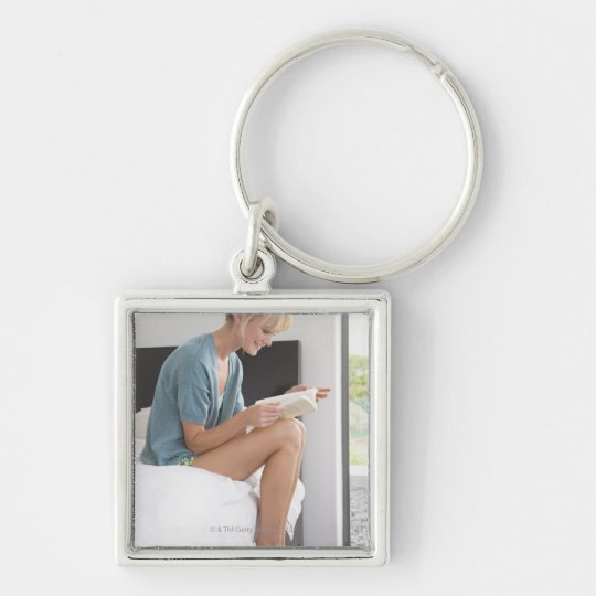 Woman reading a book on the bed keychain