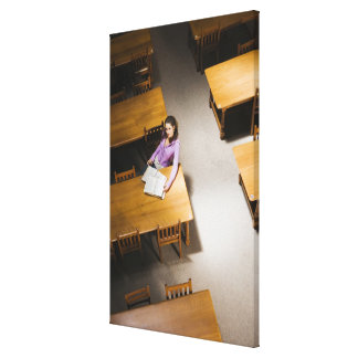Woman reading book in library canvas print