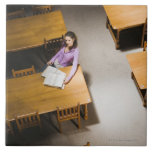 Woman reading book in library ceramic tile