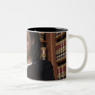 Woman reading in law library coffee mugs