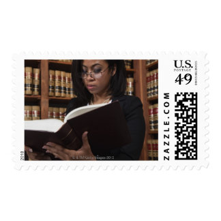 Woman reading in law library postage