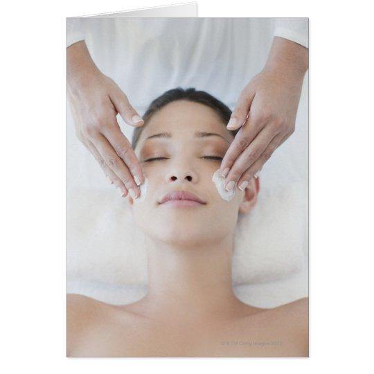 Woman receiving facial massage card