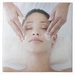 Woman receiving facial massage ceramic tile