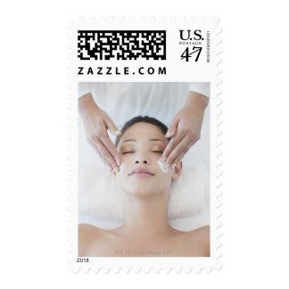 Woman receiving facial massage postage