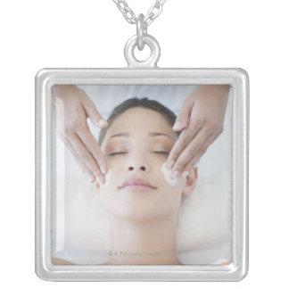 Woman receiving facial massage square pendant necklace