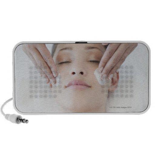 Woman receiving facial massage travel speakers