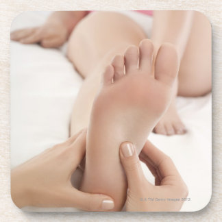 Woman receiving foot massage drink coaster