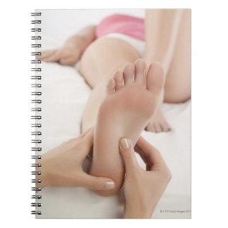 Woman receiving foot massage spiral notebook