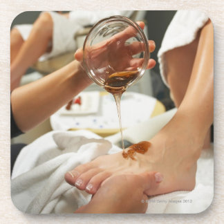 Woman receiving foot massage with oil beverage coaster