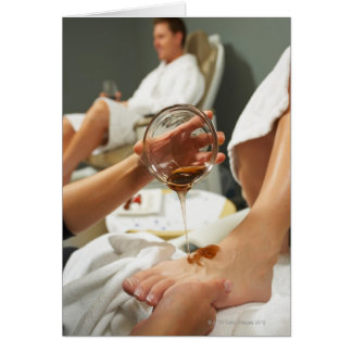 Woman receiving foot massage with oil card