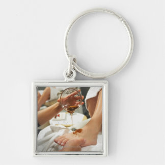 Woman receiving foot massage with oil keychain