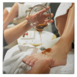 Woman receiving foot massage with oil large square tile