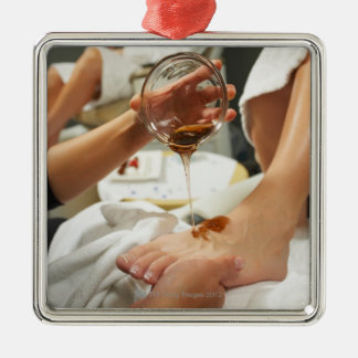 Woman receiving foot massage with oil metal ornament