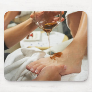 Woman receiving foot massage with oil mouse pad
