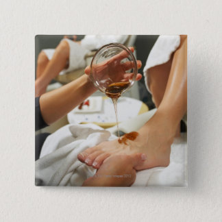 Woman receiving foot massage with oil pinback button