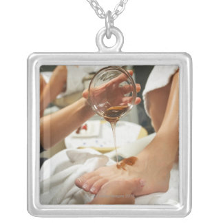 Woman receiving foot massage with oil silver plated necklace