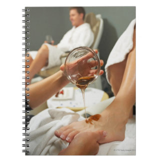 Woman receiving foot massage with oil spiral notebook