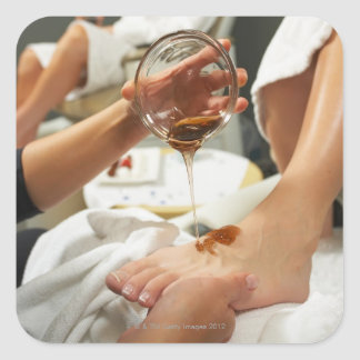 Woman receiving foot massage with oil square sticker