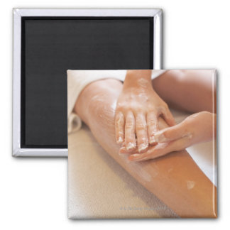 Woman receiving leg massage with lotion 2 inch square magnet