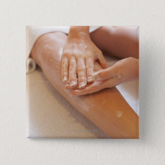Woman receiving leg massage with lotion button