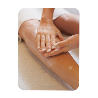 Woman receiving leg massage with lotion magnet