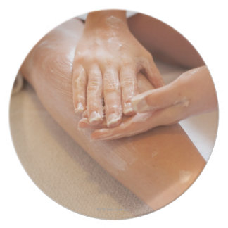 Woman receiving leg massage with lotion melamine plate