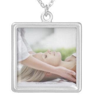 Woman receiving massage square pendant necklace