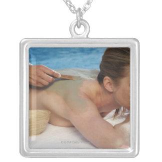 Woman receiving spa treatment, side view, close square pendant necklace