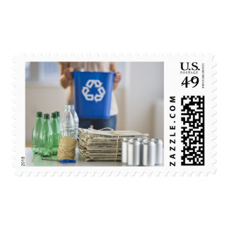 Woman recycling plastic bottles, cans and postage stamps
