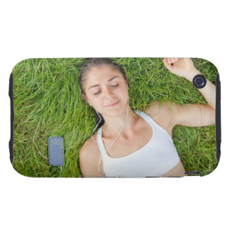 Woman relaxes with music in soft grass iPhone 3 tough case