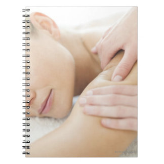Woman relaxing at a spa while receiving a 2 notebook