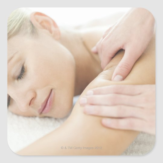 Woman relaxing at a spa while receiving a 2 square sticker