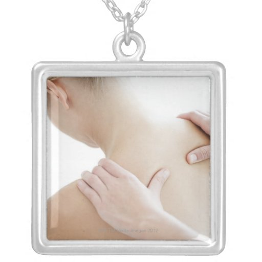 Woman relaxing at a spa while receiving a square pendant necklace